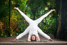 Couple yoga head stand pose stock images