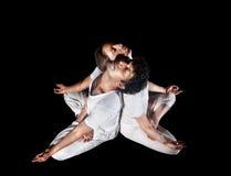 Couple yoga meditation. Of men and women in white cloth doing padmasana lotus pose with closed eyes isolated on black background stock image