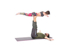 Couple in yoga pose. Fit couple in a yoga pose on a grey mat - isolated on white royalty free stock photos