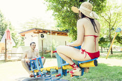 Couple of young adults have fun on a seesaw Stock Photo
