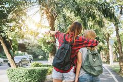 Couple of young Asian women standing along the street enjoying their city lifestyle on weekend waiting for outdoor activity. Royalty Free Stock Photography