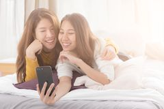 Couple of young asian women using smartphone on white bed with h stock image
