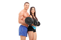 Couple of young athletes exercising with barbells Royalty Free Stock Image