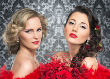 A couple of young and attractive brides in red feathers Stock Photography