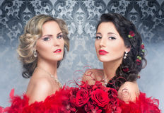 A couple of young and attractive brides in red feathers Royalty Free Stock Photos