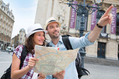 Couple of young attractive tourists watching map Stock Photos