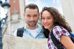 Couple of young attractive tourists watching map Royalty Free Stock Photography