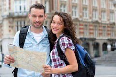 Couple of young attractive tourists watching map Royalty Free Stock Photos
