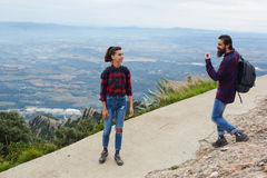 Couple of young backpackers hiking on a mountain trail Stock Photos