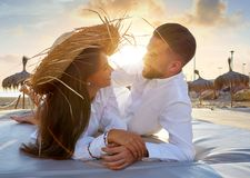 Couple young on beach lounge sunset. Vacation Stock Images