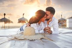 Couple young on beach lounge sunset. Vacation Stock Photography