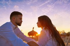 Couple young in beach vacation sunrise. Looking each other in Spain Stock Image