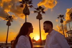 Couple young in beach vacation sunrise. Looking each other in Spain Royalty Free Stock Photos