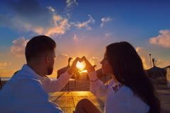 Couple young in beach vacation sunrise. Couple young heart symbol with hands at the beach vacation sunrise in Spain Royalty Free Stock Images