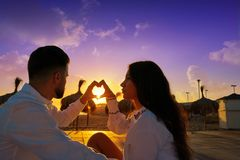 Couple young in beach vacation sunrise. Couple young heart symbol with hands at the beach vacation sunrise in Spain Royalty Free Stock Photos