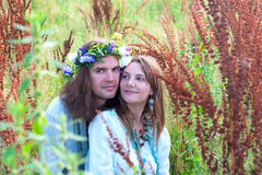 Couple young beautiful hippies. In the bush grass Stock Images
