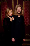 Couple of young blond people dressed in black in a dark room Stock Photography