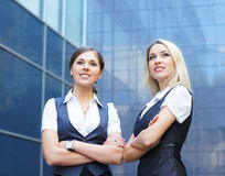 A couple of young business women in formal clothes. A couple of young and happy Caucasian business women posing in formal clothes. The image is taken on a modern Royalty Free Stock Photography