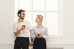 Couple of young colleagues drink coffee near window Stock Photo