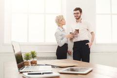 Couple of young colleagues drink coffee near window Royalty Free Stock Photo