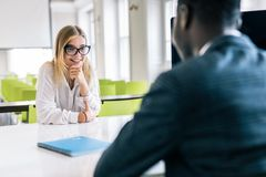 Couple of young colleagues working in modern office. Cheerful man hr interviewing female candidate, copy space royalty free stock images