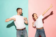 A couple of young man and woman dancing hip-hop at studio. A couple of young funny and happy man and woman dancing hip-hop at studio on blue and pink trendy royalty free stock image