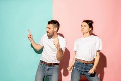 A couple of young man and woman dancing hip-hop at studio. A couple of young funny and happy man and woman dancing hip-hop at studio on blue and pink trendy stock photos