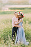 Couple of young happy people embracing in the meadow. Royalty Free Stock Photos