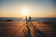 Couple of young hipsters cycling together at the beach at sunrise sky at wooden deck summer time.  royalty free stock photos
