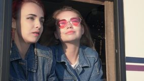 Couple young indie style women that looking to outside from window Wind blow hair Sun tickle eyes at end of the day. Couple young indie style women that looking stock video footage