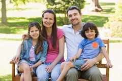Couple with young kids sitting on park bench Royalty Free Stock Image