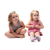 Couple of young little girl sitting over  white background Royalty Free Stock Photography