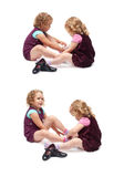 Couple of young little girls sitting over isolated white background Stock Photo