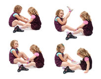 Couple of young little girls sitting over isolated white background Stock Photos