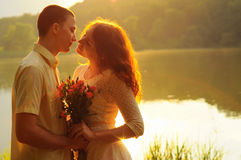 Couple of young lovers hugging in the sunset light Stock Images