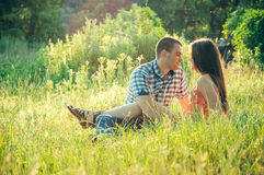 Couple of young lovers sitting on the grass Royalty Free Stock Images