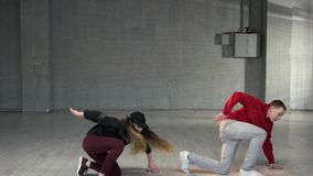 Couple of young man and woman dancing hip-hop. Two teenagers in casual outfit performing contemporary dance. Workout in dance studio stock video