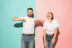 A couple of young man and woman dancing hip-hop at studio. A couple of young funny and happy man and woman dancing hip-hop at studio on blue and pink trendy royalty free stock photography