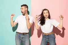A couple of young man and woman dancing hip-hop at studio. A couple of young funny and happy man and woman dancing hip-hop at studio on blue and pink trendy stock images