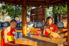 A couple of young monks sit and rest outside the temple, Thailand. royalty free stock photos
