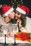 Couple young near decorated Christmas tree celebrating New Year Royalty Free Stock Images