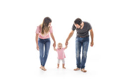 Couple of young parents helping their baby to make first steps on floor in their home Stock Photos