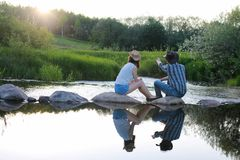 Couple of young people admire the sunset in the spring evening o stock images