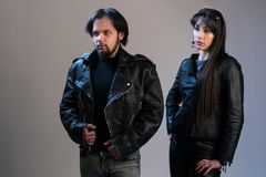 A couple of young people in black leather jackets. A guy and a girl in rocker or biker style posing in the studio. royalty free stock image