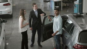 The couple of young people buys a car in car showroom. The manager in suit gives the keys from car to a swarthy man. Happy guy with keys demonstrates it on stock footage