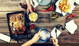 Couple of young people at the dinner table with a variety of foods, baked chicken legs, potatoes barbecue, beer, pickles and snack stock photo