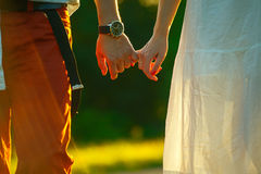 Couple of young people holding hands and walks away into the sun. Couple holding hands walking on the field Royalty Free Stock Photo