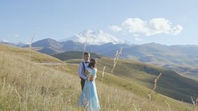 Couple of young people hugging against the background of mountains. Slow mo stock video footage