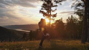 Couple of young people in love at sunset. A woman in the arms of her man on top of a mountain. stock footage