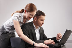 Couple of young people in the office working toget Stock Photos